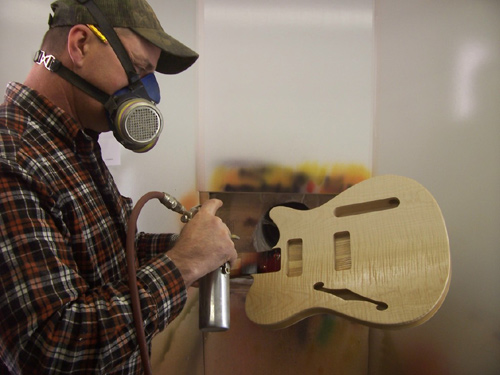 Jeff Neville spraying a guitar body